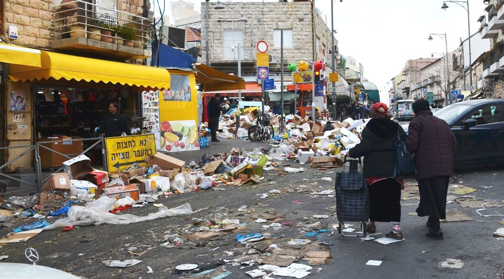 Near Machane Yehuda market women try to cross Agrippas Street filled with garbage