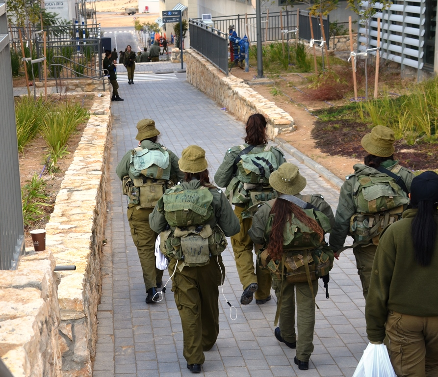 Female IDF soldiers walking in army base with backpacks