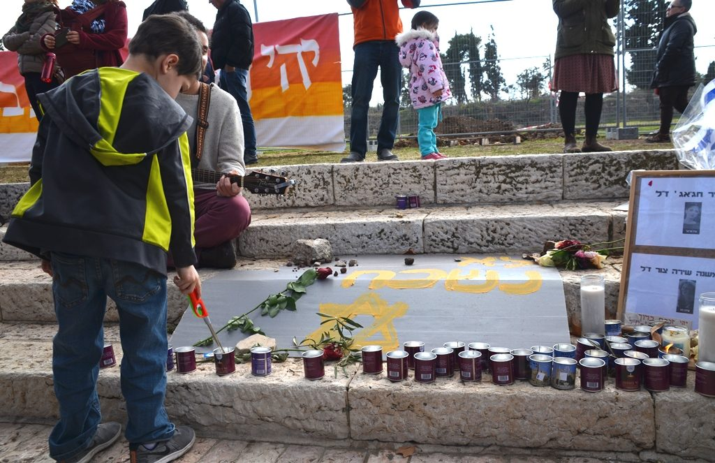Boy lighting memorial candle site 4 young Israelis killed