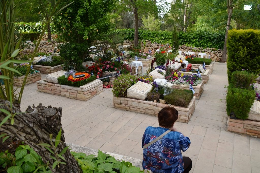 Woman sitting near graves of Har Herzl military cemetery Yom Hazikron