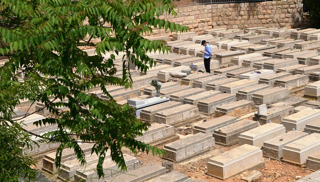 One man standing by old grave in Jerusalem cemetery on Yom Hazikaron