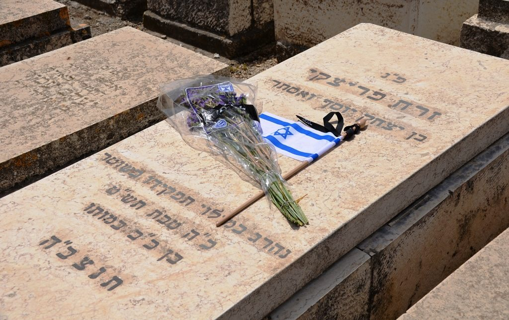 Flowers, Israeli flag and black yizkor ribbon on 1948 grave