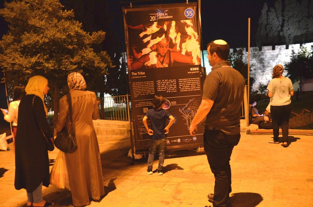 People looking at sign for fire and dance show Jerusalem Light Festival