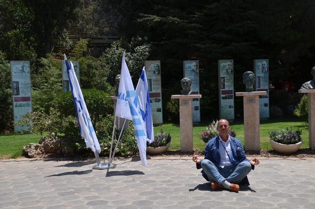Flags for Maccabiah outside Beit Hanasi in gardens with man representing South Korea sitting on ground