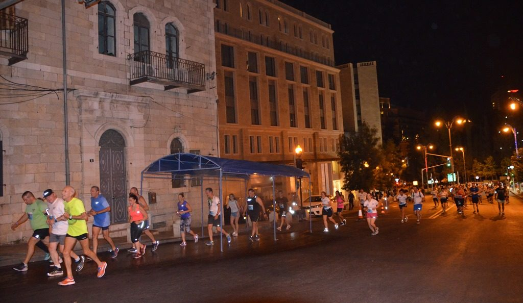 Runners Jerusalem Maccabiah Night Run shower near end of route