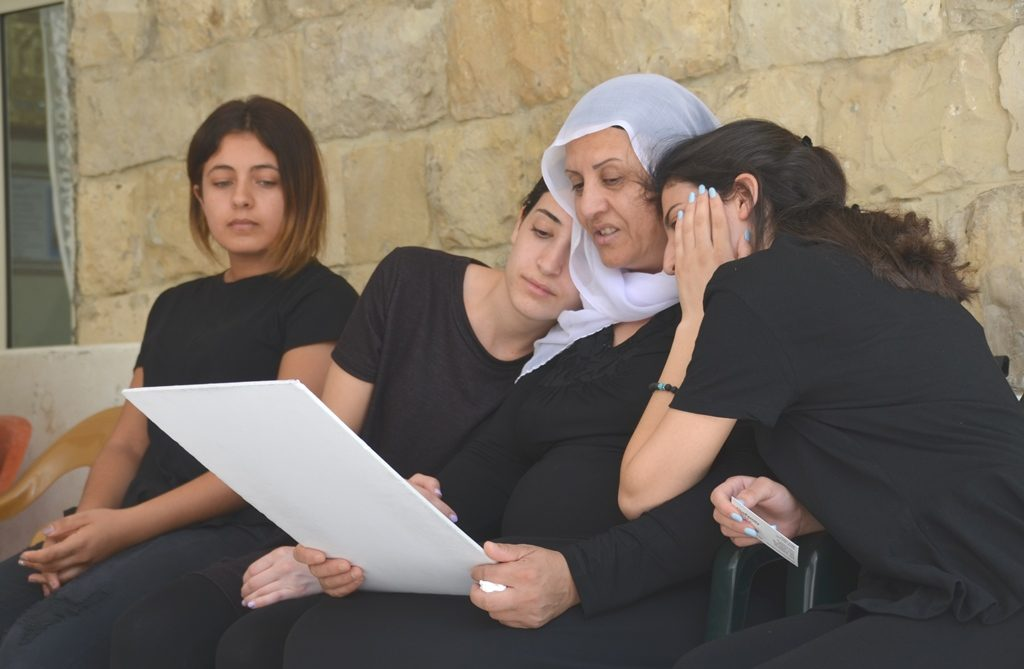 Family of Kamil Shnaan look at his photo during memorial visit by Jews and others in Horfeish
