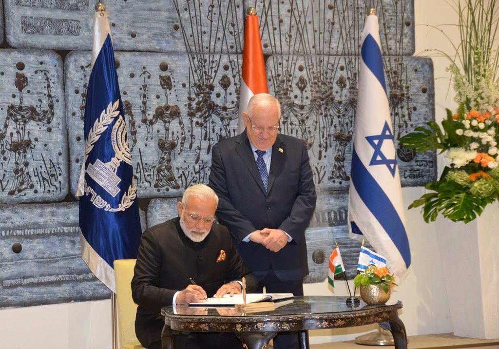 Modi signing guest book with President Reuven Rivlin watching