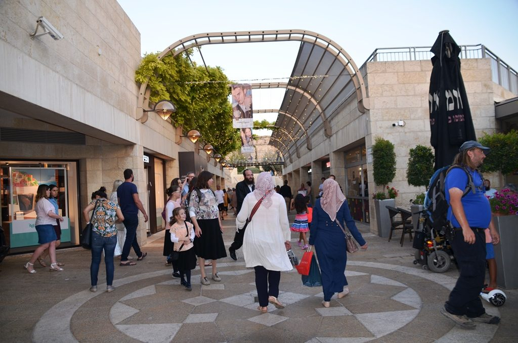 Two Muslim women in Mamilla Mall walking in crowd Jerusalem Israel