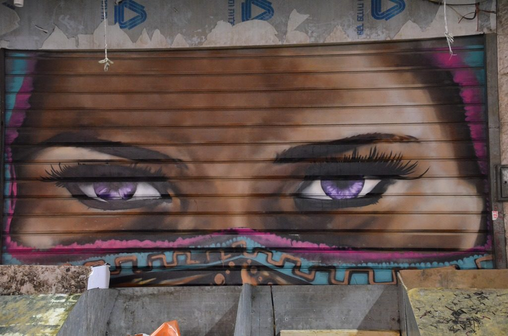shuk Machane Yehuda Market Jerusalem Israel shuttered painted with women's eyes looking over display tables