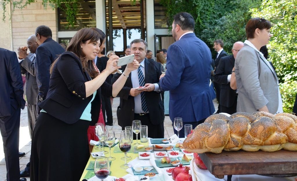 Tzipi Hotovely taking a photo of the food at Beit Hanasi