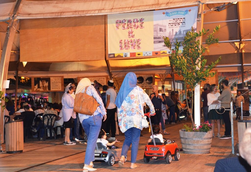 Muslim women walk pushing children in little cars in Jerusalem Israel First Station, Hatakana tourist site