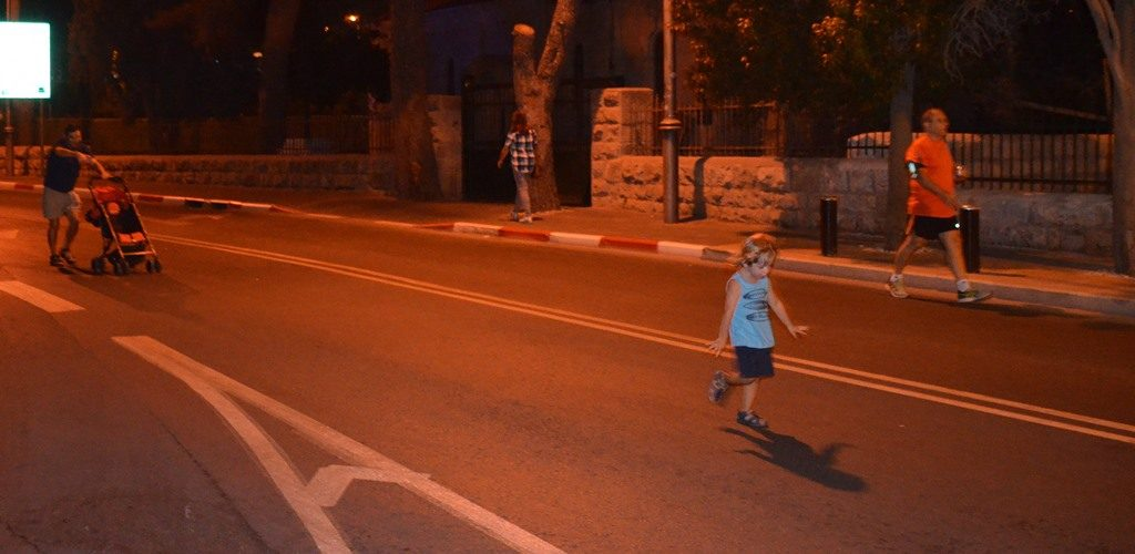 Jerusalem Israel Women's Night Races young child and father follow running in closed street