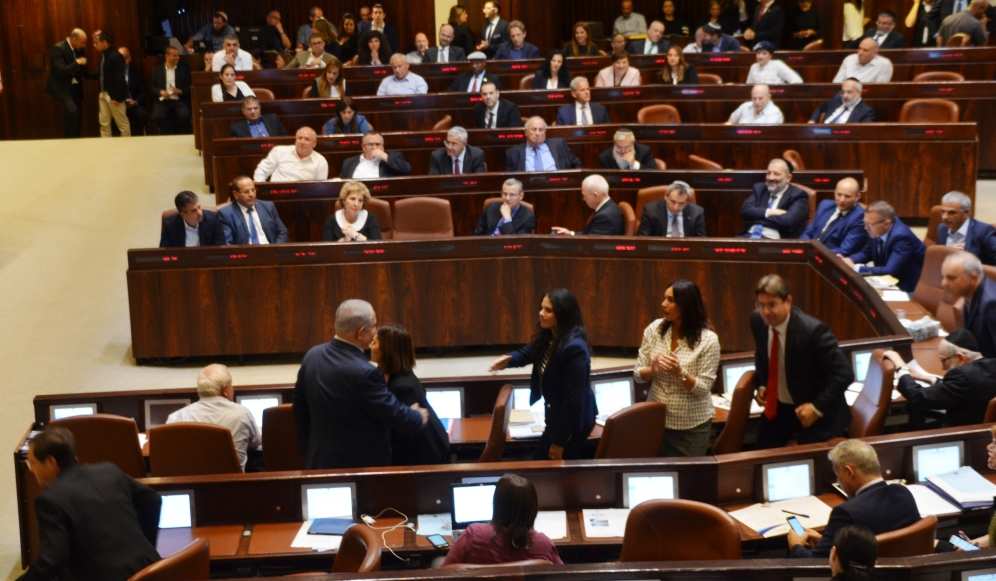 Prime Minister Netanyahu goes to sit down after speaking at Knesset