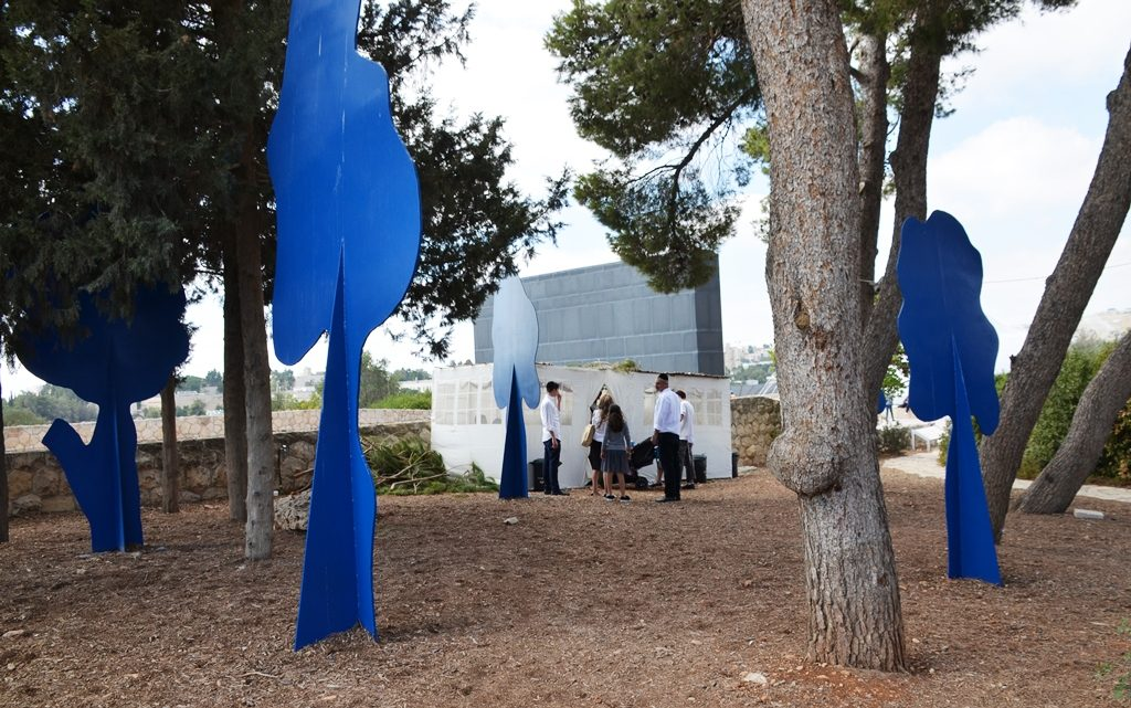 Sculpture at Israel Museum with sukkah in background open for visitors to use