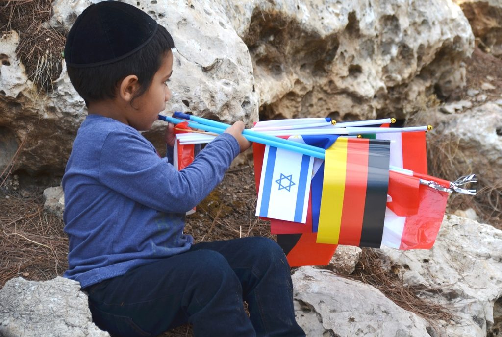 Little boy in Jerusalem with international flags collected at Jerusalem Parade