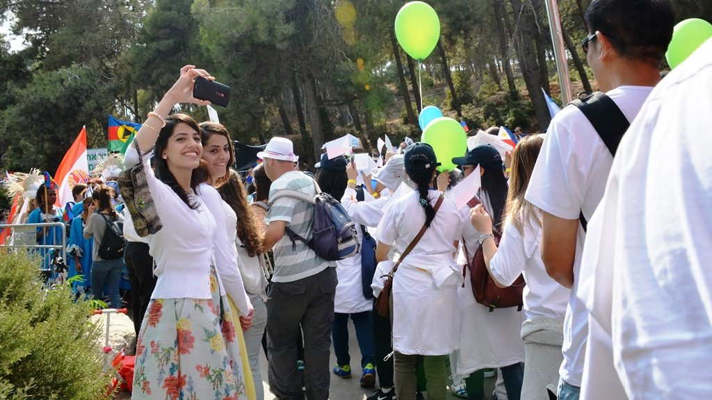 Two women taking selfies in park as Jerusalem March participants go to walk