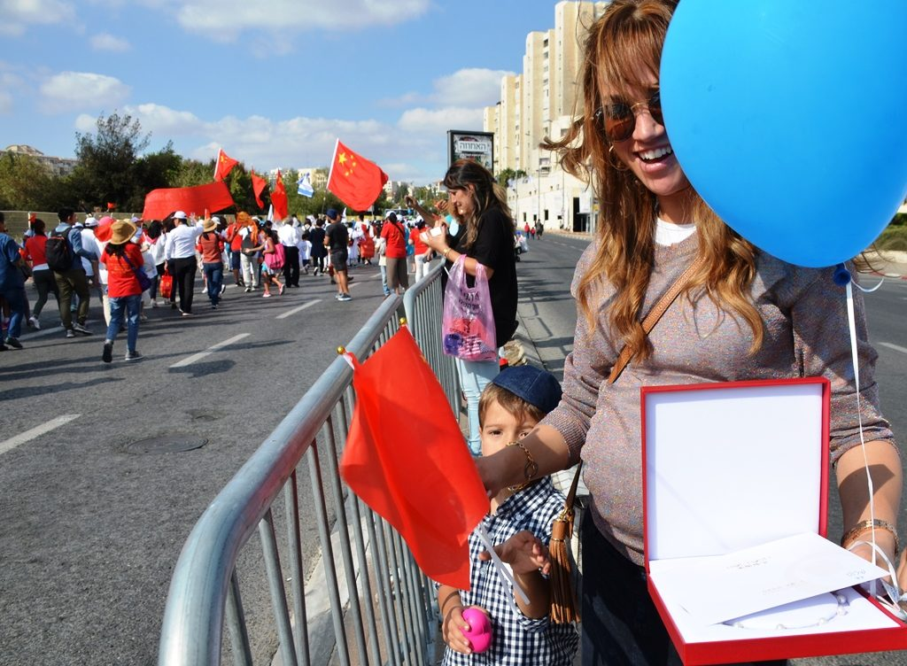 Young woman got a necklace from woman from China walking in parade