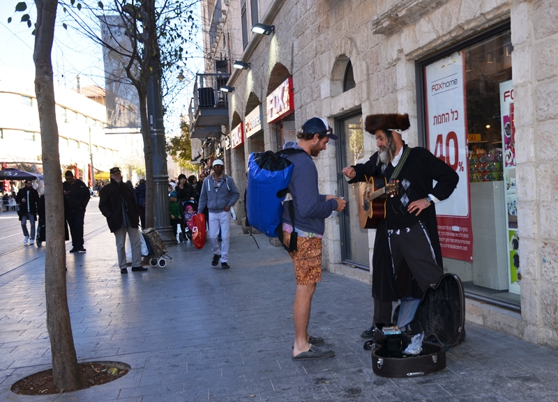 Two men on Jaffa Street, one in shorts other religious musician