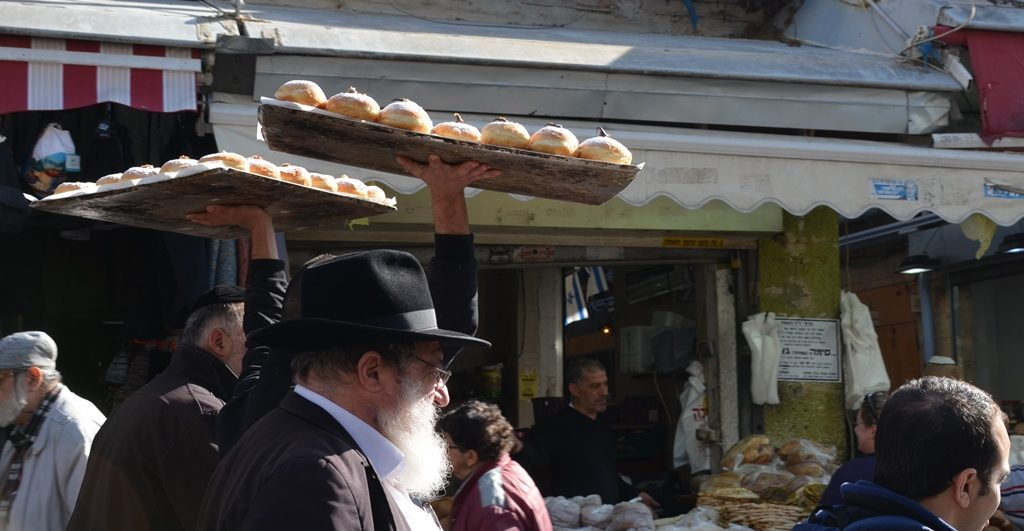 Donuts on large tray carried by man through shuk before Hanukkah