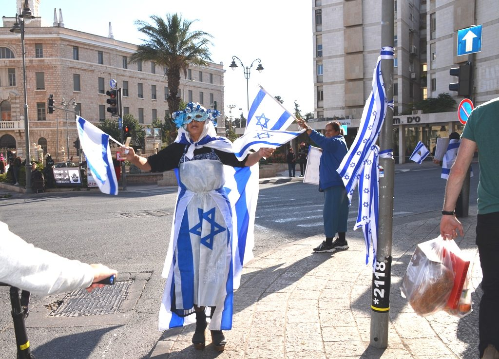 Counter protester against Women in Black is dressed in Israeli flag