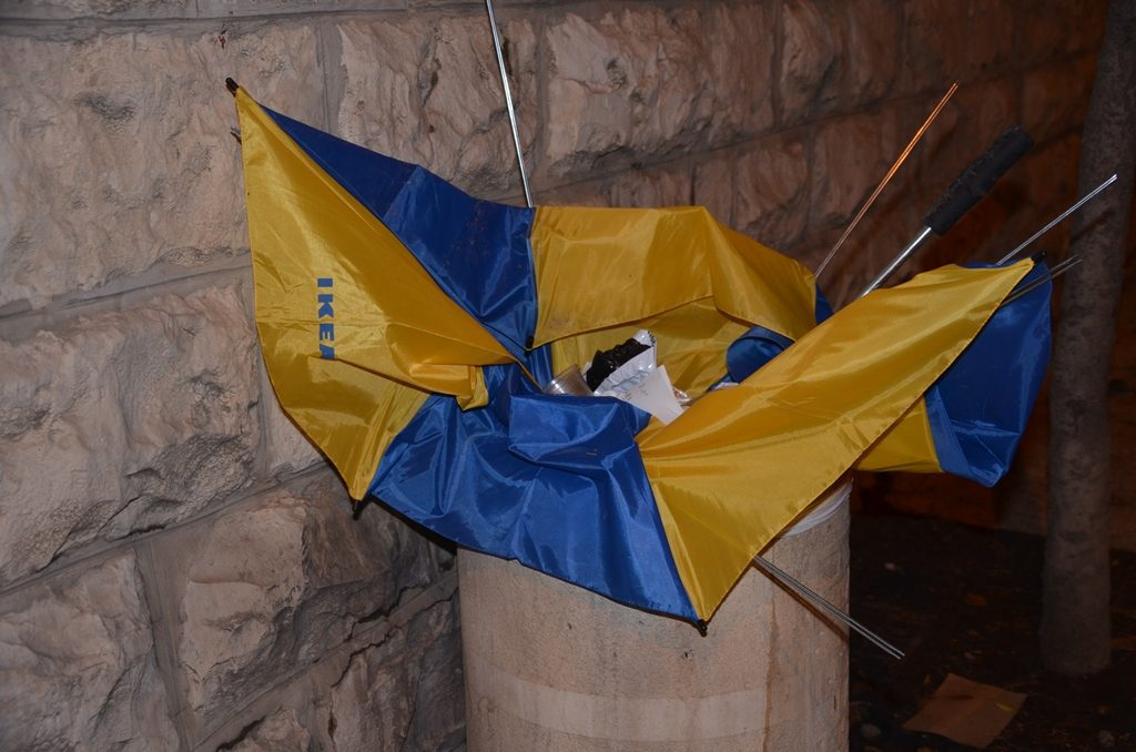 Broken IKEA umbrella in street garbage bin after heavy rain.