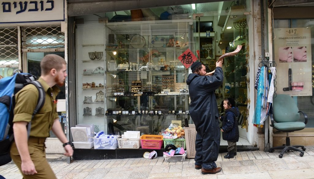 Man blowing shofar and son watches and soldier passes by