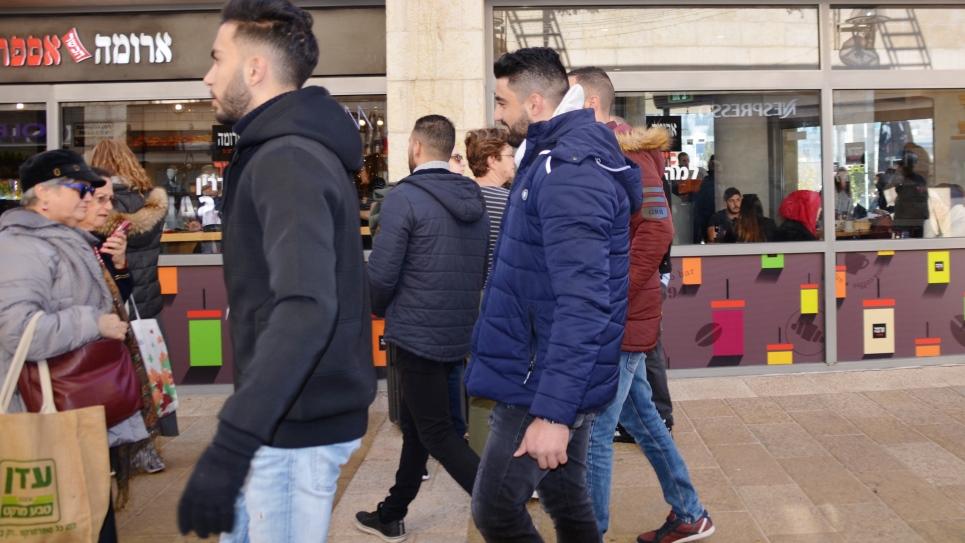 People walking in Jerusalem Israel Mamilla Mall past Arab women sitting in cafe