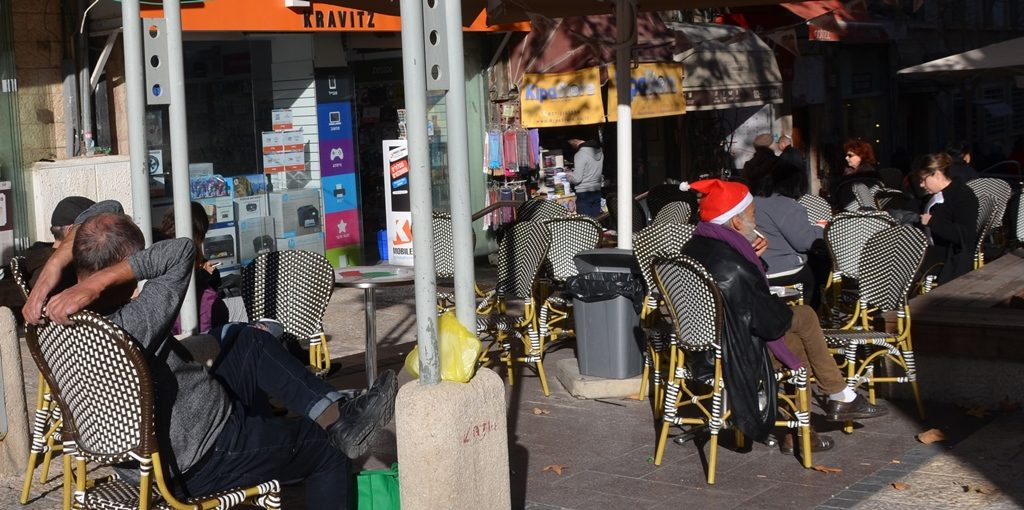 Man smoking on Ben Yehuda wearing red Santa helper hat