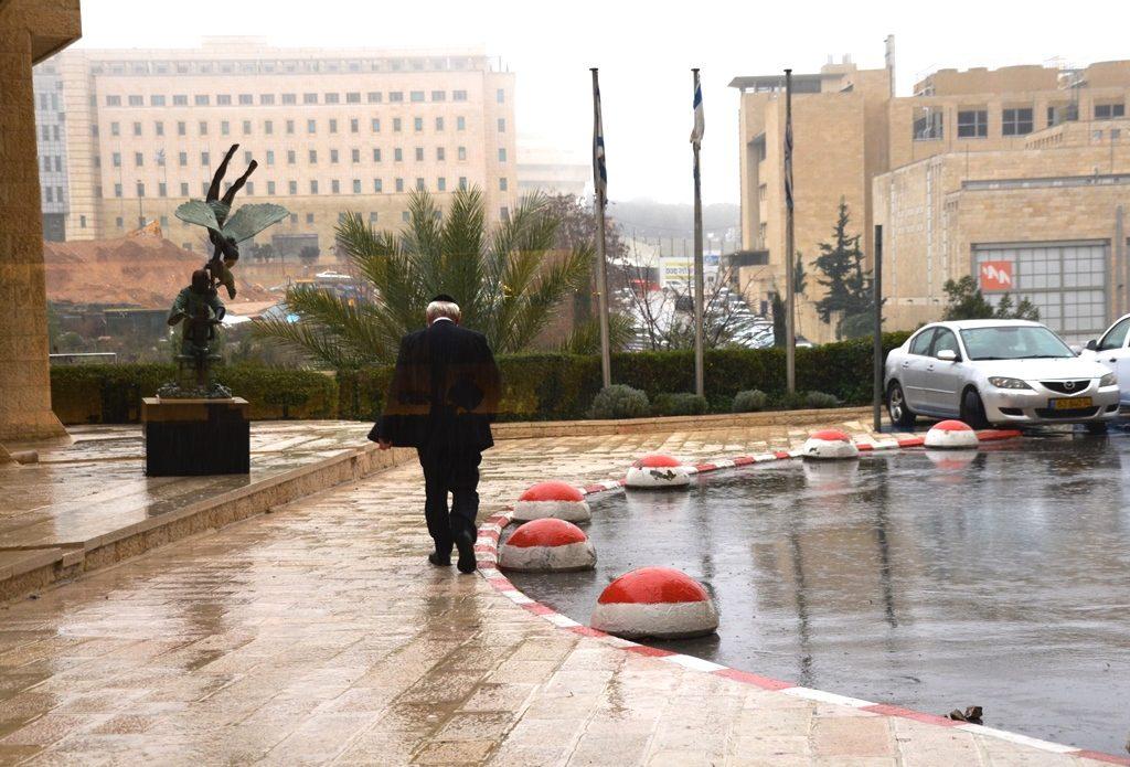 Wet sidewalks outside Ramada Hotel as man walks away without coat.