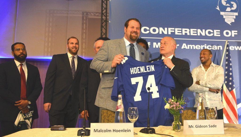 Malcolm Hoenlein looks up at Jewish football player Geoff Schwartz at CoP dinner in Jerusalem Israel