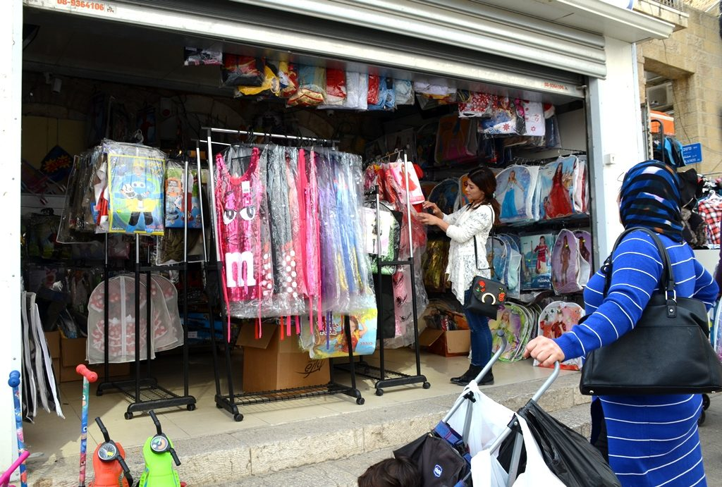 Purim costumes for children on Agrippas Street in Jerusalem, Israel Arab woman looking at dresses