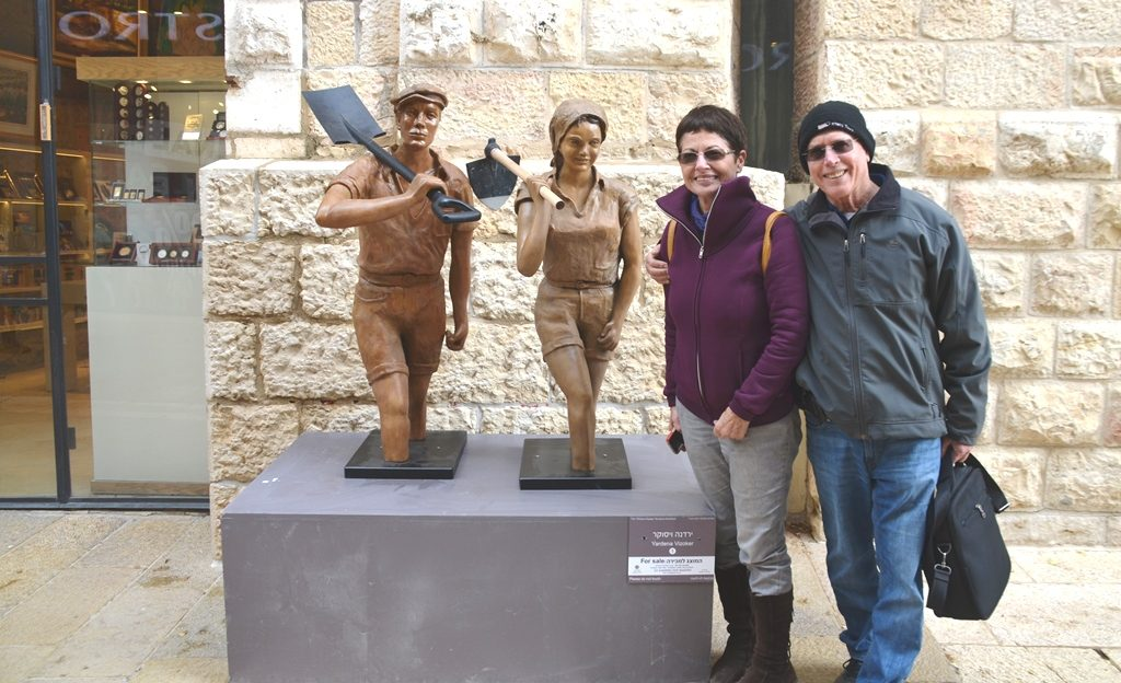 Mamilla Mall artist Yardena Yizoker with her sculpture of male and female Israeli pioneers