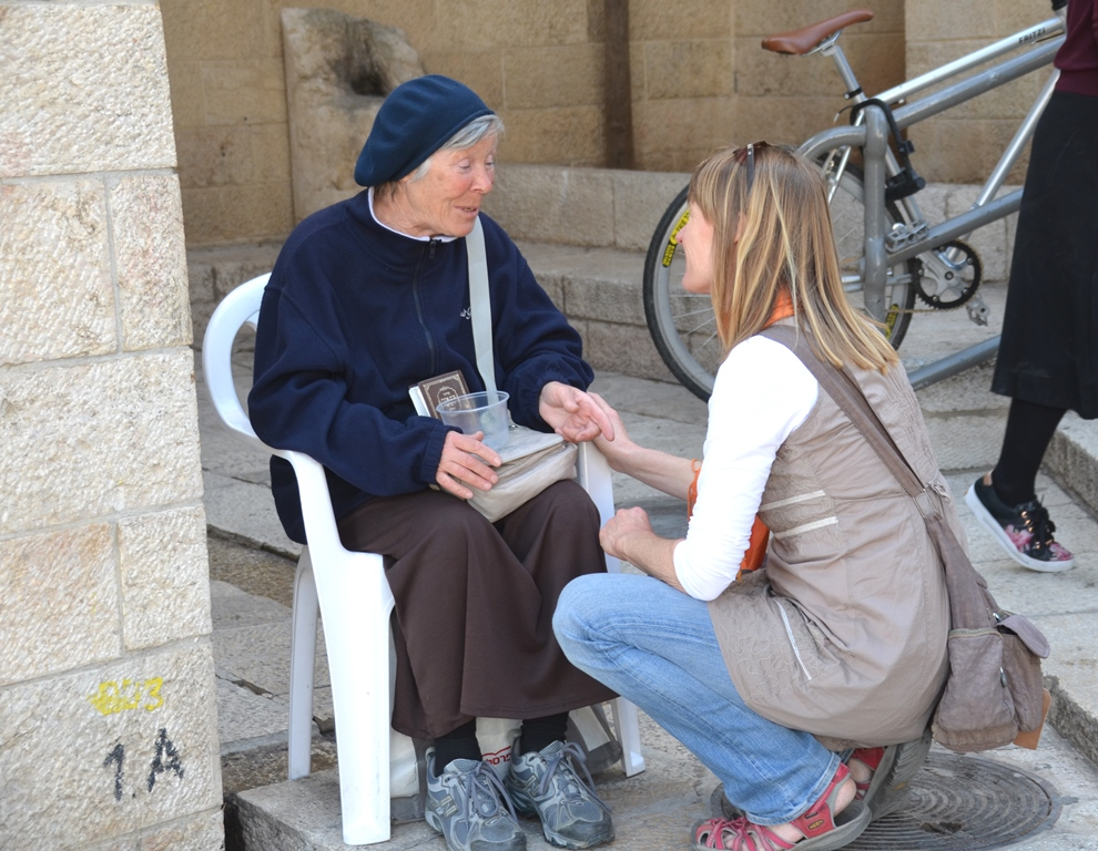 Female beggar sitting in chair and young woman stops to chat with her