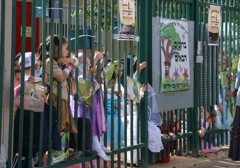 Children behind school gate dressed in Purim costumes Israel