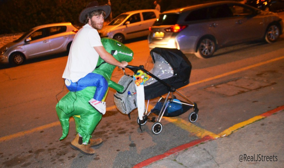 Man dressed in costume pushing baby carriage.. Purim in Jerusalem