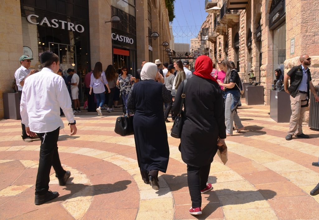Pesach crowd in Mamilla Mall in Jerusalem, Israel, with two Muslim women walking through the mall