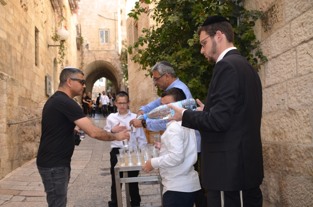 Volunteers pouring water to give away to visitors to Old City on Pesach