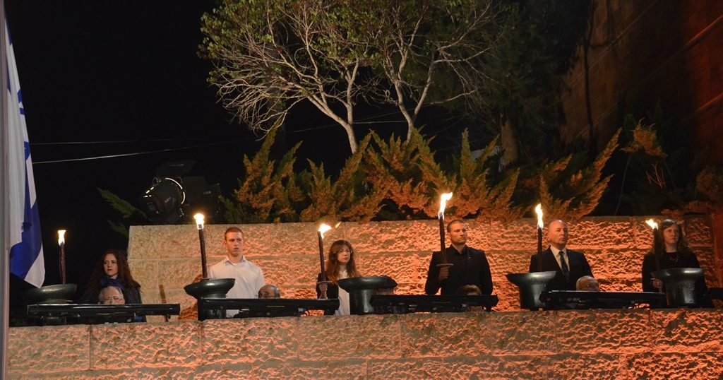 Survivors and young relative lighting flame at Yad Vashem on Yom HaShoah