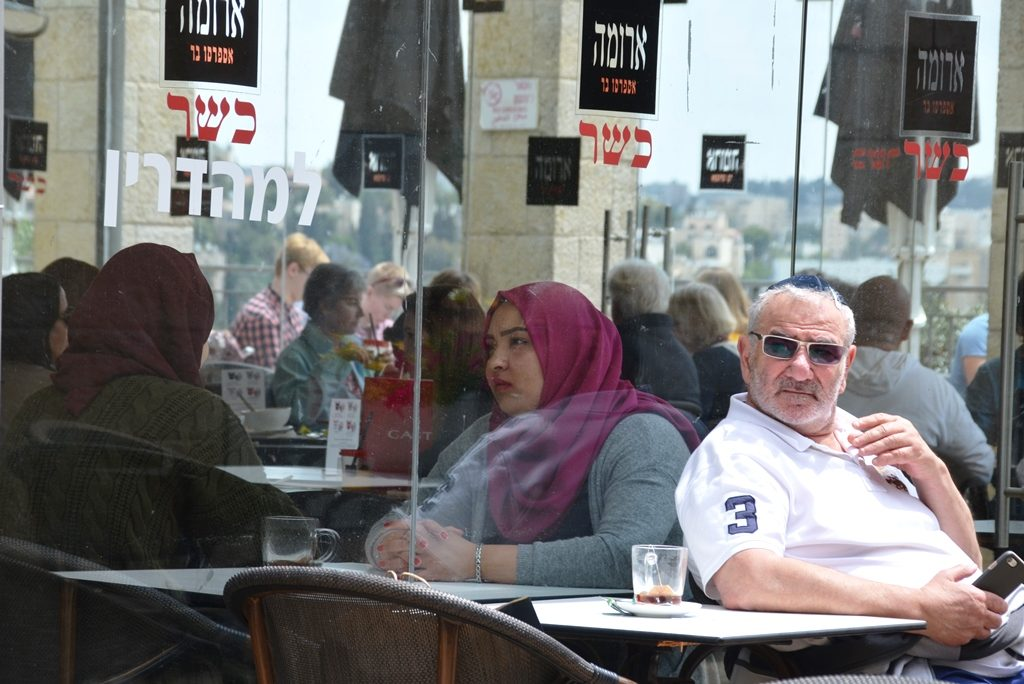 Two women wearing hijab sit inside Aroma Cafe in Jerusalem Israel Mailla Mall on Jerusalem Day