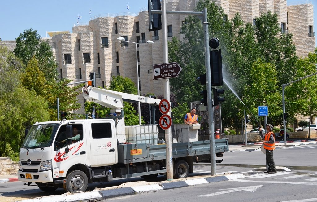 Two men washing traffic lights in Jerusalem