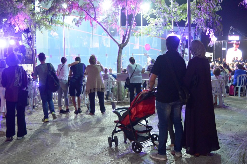Arab couple and children watching Squash Tournament in Jerusalem Israel near Jaffa Gate