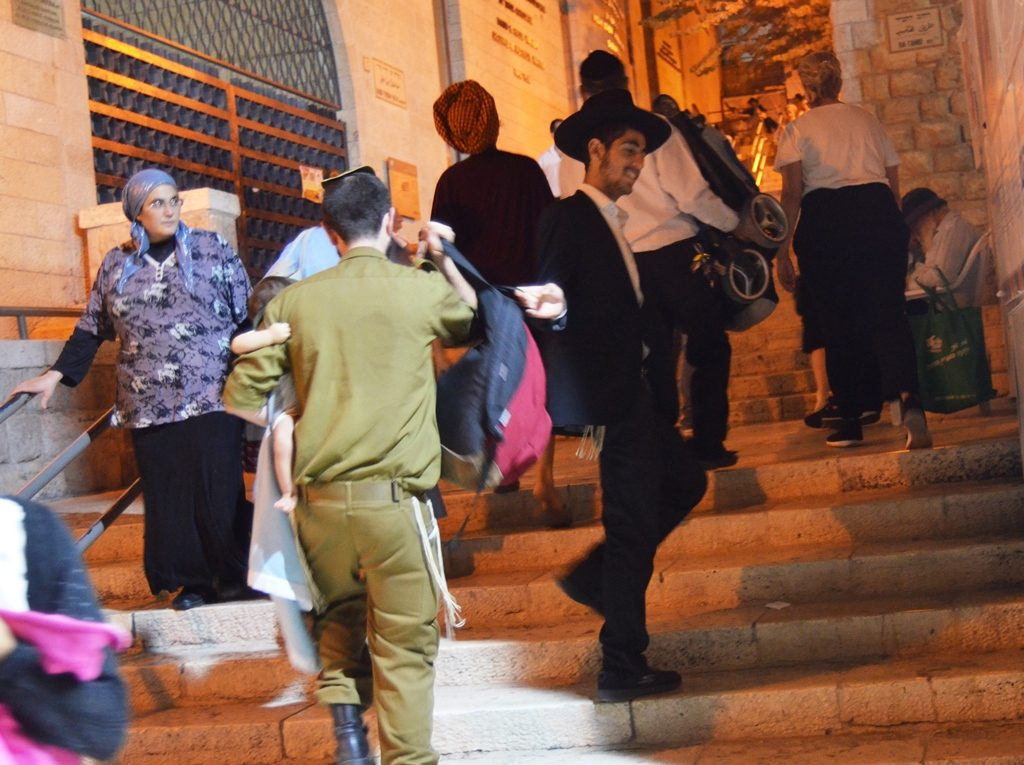 IDF soldier carrying a baby being helped by Haredi men near Kotel on stairs
