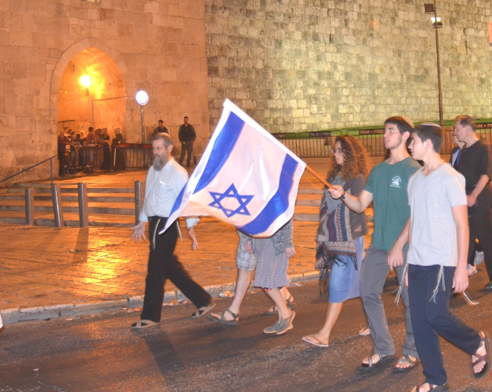 People with Israeli flag walking by Flowers Gate Old City Jerusalem Israel