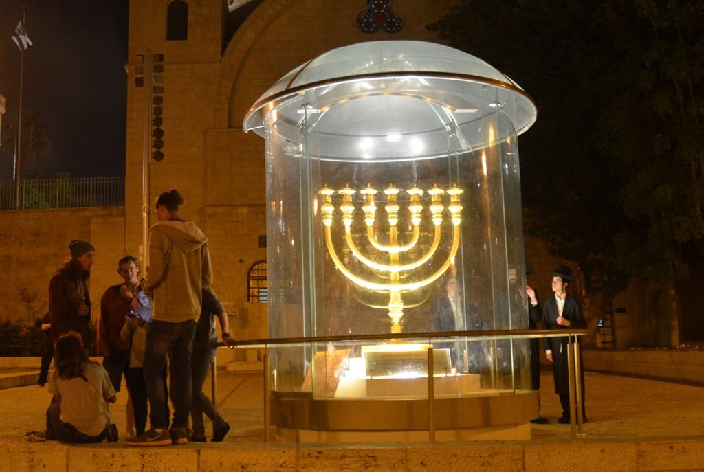 Temple menorah lit at night in front of Hurva Synagogue on Tisha B'Av night