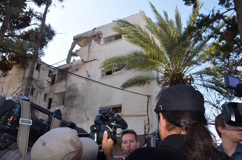 Micky Rosenfeld talking to media near building damaged by Hamas rocket