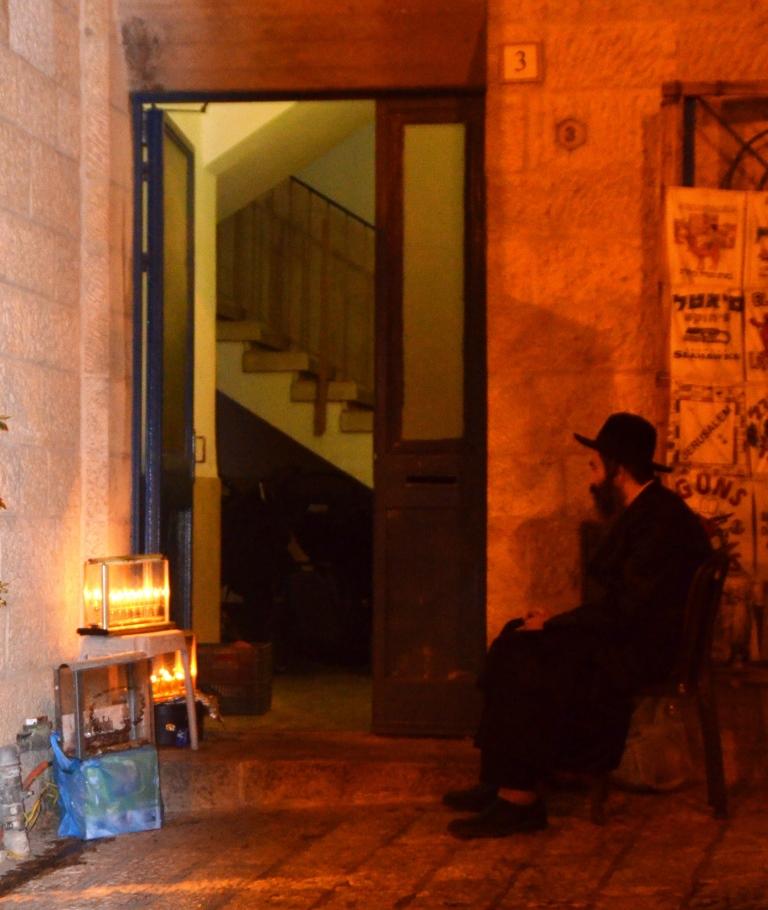Jerusalem Old City man sitting watching Hanukkah lights