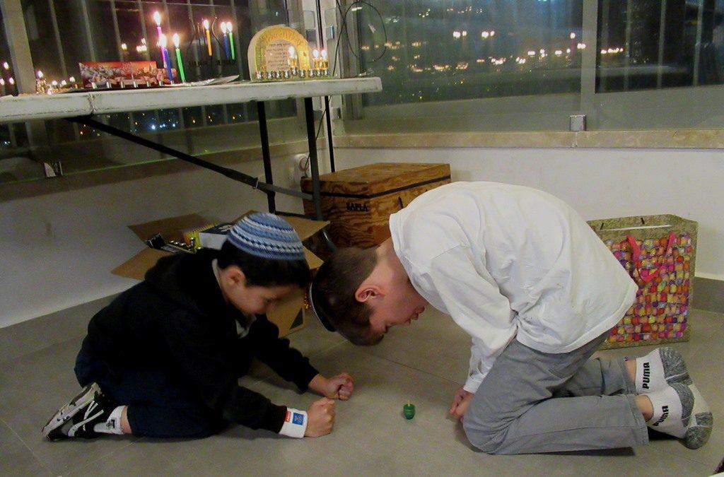Dreydl played by tow boys on the floor on Hanukkah