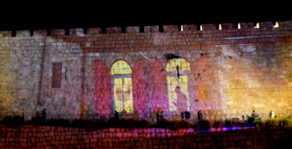 Man lighting candles at home photo projected on Old City Wall in Jerusalem Israel for Hanukkah