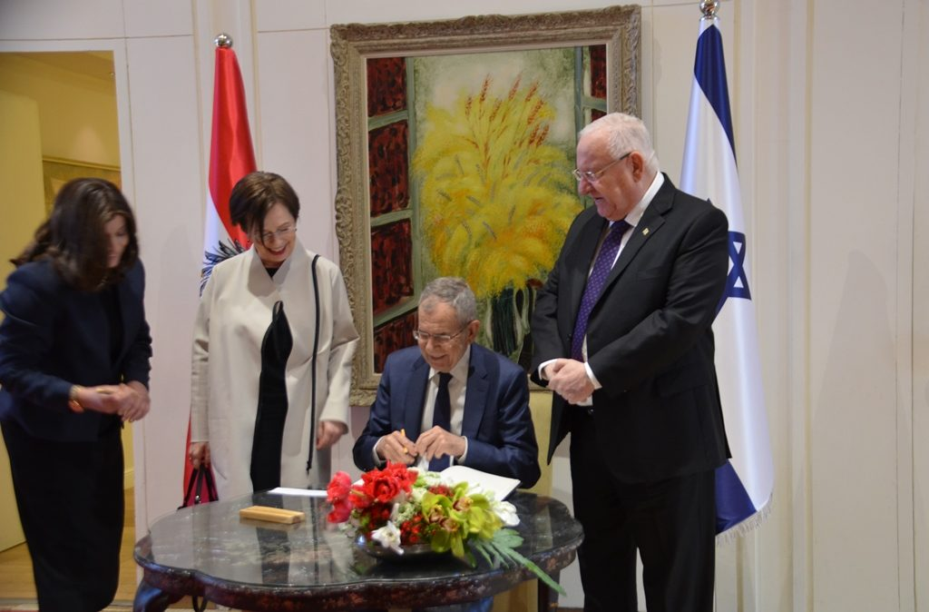President of Austria signs guest book as his wife and President Rivlin watch