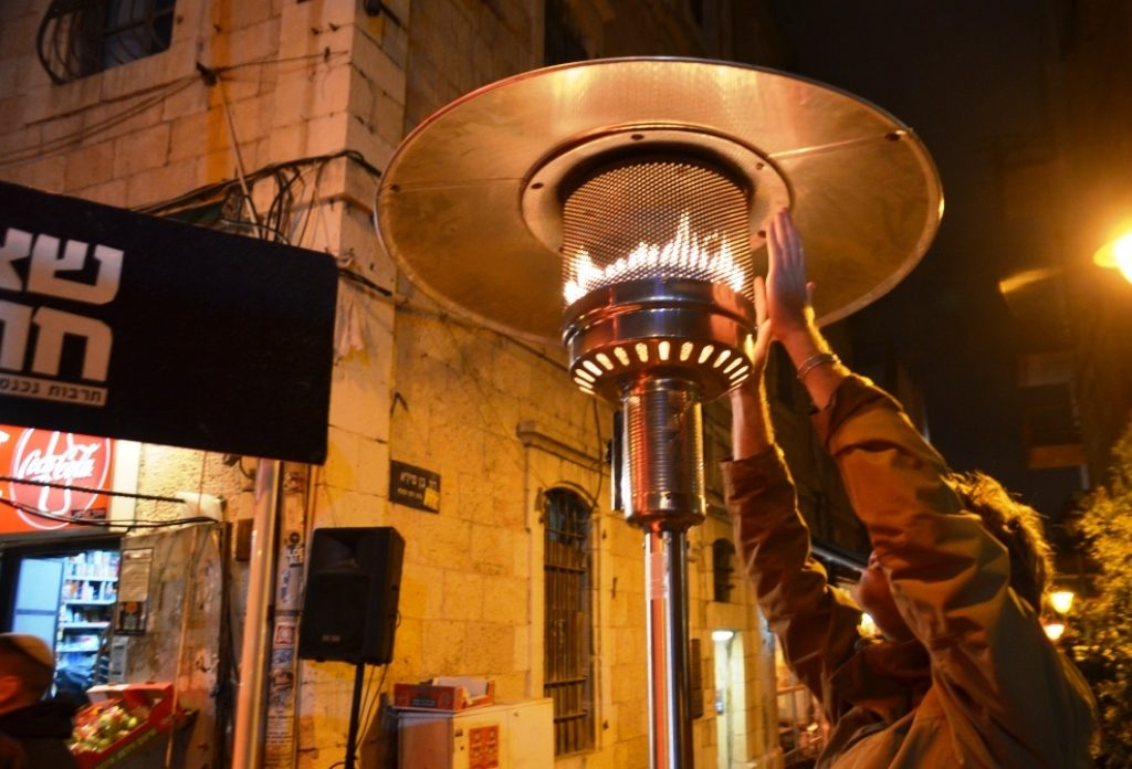 Man warming his hands at night during Jerusalem Winter Noise Festival
